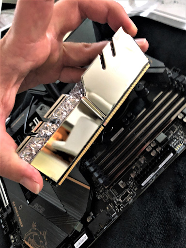 Holding a new RAM module by its edges in order to insert it into a PC