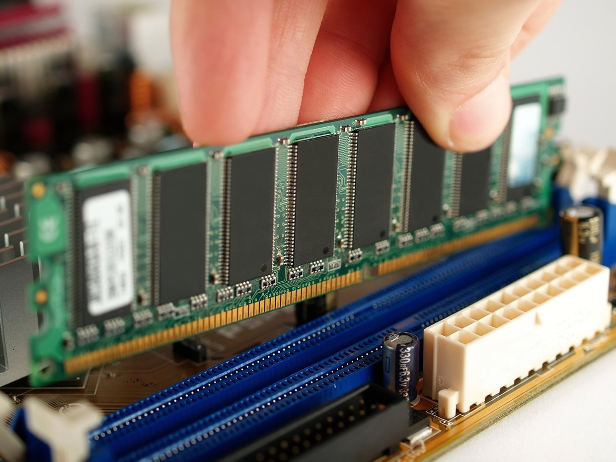 Inserting RAM sticks into a computer's motherboard.